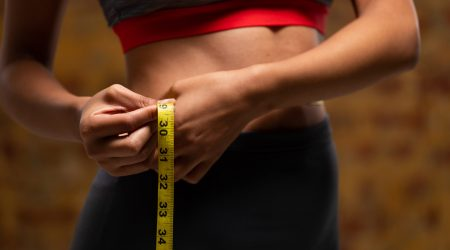 Side view mid section of a fit mixed race woman wearing sportswear and measuring her waist with measuring tape with brick wall in the background.